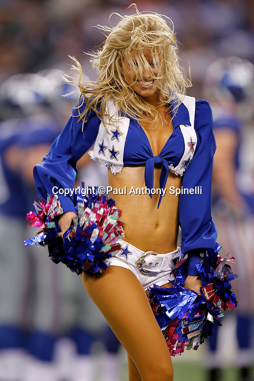 A Dallas Cowboys cheerleader flips her hair and waves her pom poms as she does a dance routine during the NFL week 7 football game against the New York Giants on Monday, October 25, 2010 in Arlington, Texas. The Giants won the game 41-35. (©Paul Anthony Spinelli)