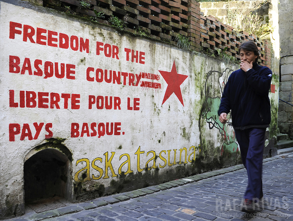 an unidentified man walks past a pro independence mural painting in the northern Spanish Basque village of Pasajes de San Pedro, on February 18, 2009.