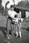 young farmer with son and a little goat posing 1950s