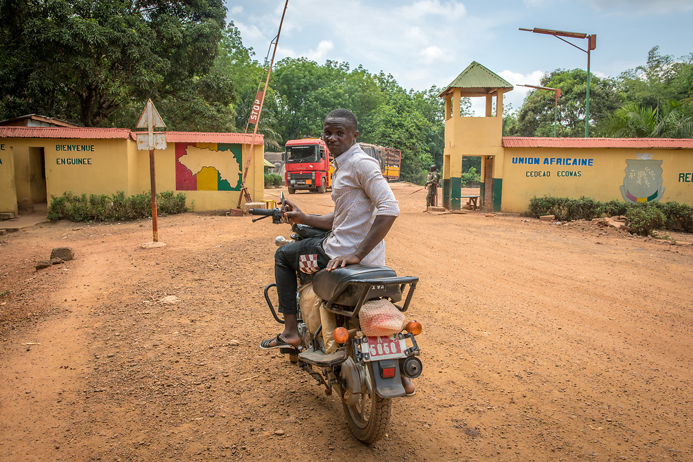 Adult African male sits on motorcycle in front of border entrance into the Republic of Guinea