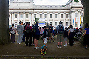 Watching live TV coverage of Equestrian events, spectators and other sports fans stand or sit in summer deckchairs at the old Royal Naval College, Greenwich on day 4 of the London 2012 Olympic Games. Greenwich Park is hosting the Olympic Equestrian competitions, plus the combined running and shooting event of the Modern Pentathlon. The Old Royal Naval College is the architectural centrepiece of Maritime Greenwich, a World Heritage Site in Greenwich, London. The buildings were originally constructed to serve as the Royal Hospital for Seamen at Greenwich, now generally known as Greenwich Hospital, which was designed by Christopher Wren, and built between 1696 and 1712.