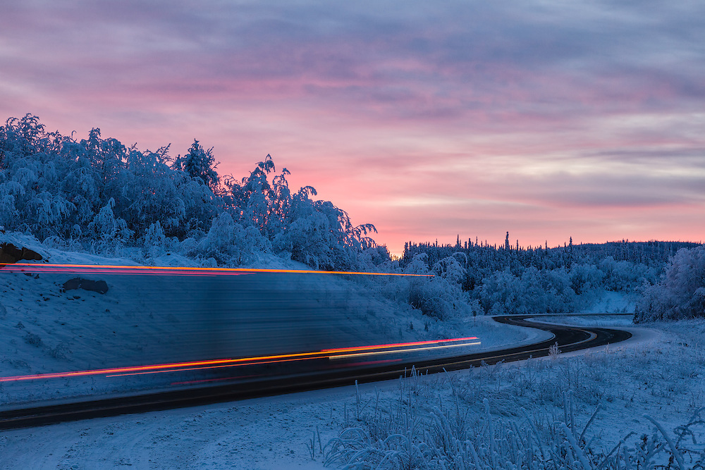 Lights from a truck on the Alaksa Highway are captured as a blur during this long exposure of sunrise somewhere near the border with Canada.  Winter. Morning.
