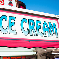 Picture of carnival ice cream sign on a food stand at a county fair.