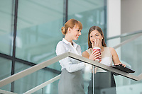 Businesswomen gossiping while having coffee on steps in office