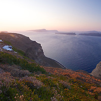 The winds blows on the waters of the Aegean as the sun sets on the horizon, casting it's golden light on the white washed houses hugging the cliffs of Akrotiri.