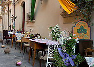 Trattoria La Foglia, a restaurant with olf fashioned tables on the street in Ortigia, Syracuse, Sicily, Italy