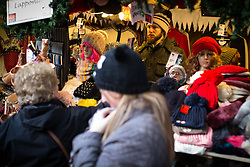 © Licensed to London News Pictures . Manchester , UK . A woman reflected in a mirror at a woolly hat stall . FILE PHOTO DATED 20/11/2013 of Christmas Markets in Manchester as temperatures drop and 2014 seasonal markets start up across the country , selling mulled wine , german hot dogs , dutch pancakes , wooly hats and many other festive frivolities . Christmas markets provide an economic boost to many city centres and create a festive atmosphere on otherwise cold and dark nights . . Photo credit : Joel Goodman/LNP