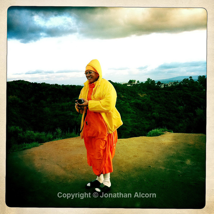 A Buddhist monk takes photos on a hillside in Hollywood.