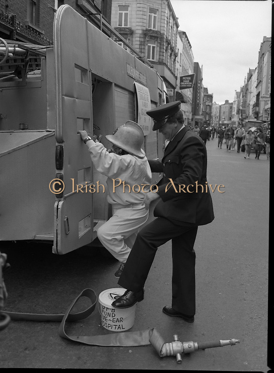 Maureen Potter with The Dublin Fire Brigade..1986..19.07.1986..07.19.1986..19th July 1986..Dublin Fire Brigade aided and abetted by Maureen Potter staged a collection,today,in aid of The Royal Victoria Eye and Ear Hospital,Adelaide Road,Dublin. It is hoped that the proceeds would go towards the purchase of a laser eye scanner. The Eye and Ear Hospital was established in 1897 and has served not only Dublin but the whole country as well...It's a long way down. Picture shows Maureen ,getting assistance from a Dublin Fireman,as she descends from the fire tender.