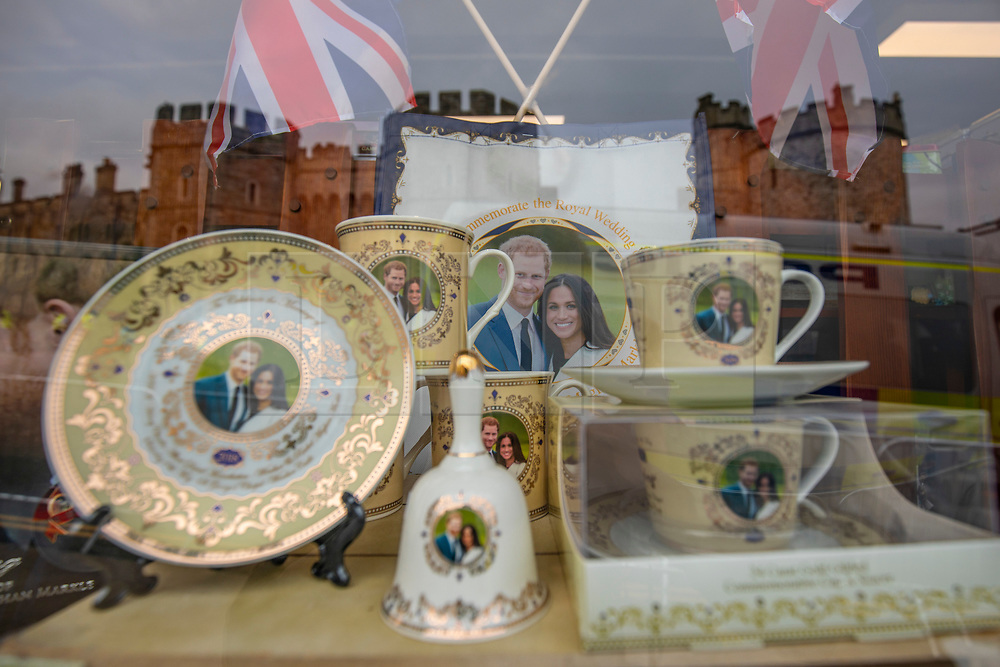 © Licensed to London News Pictures. 16/05/2018. Windsor, UK. Royal Wedding memorabilia is seen in a shop window in Windsor with Windsor Castle reflected in the background. Prince Harry and Meghan Markle are to be married on Saturday in Windsor. Photo credit: Rob Pinney/LNP