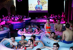 © Licensed to London News Pictures. 07/06/2014. LONDON, UK. People watching 'Napoleon Dynamite' film in hot tubs as they attend 'Hot Tub Underground Cinema' at former Shoreditch Underground station in east London on Saturday, 8 June 2014. Visitors of the unique cinema enjoy a Jacuzzi with friends during classic films such as Moulin Rouge and Snatch. Photo credit : Tolga Akmen/LNP