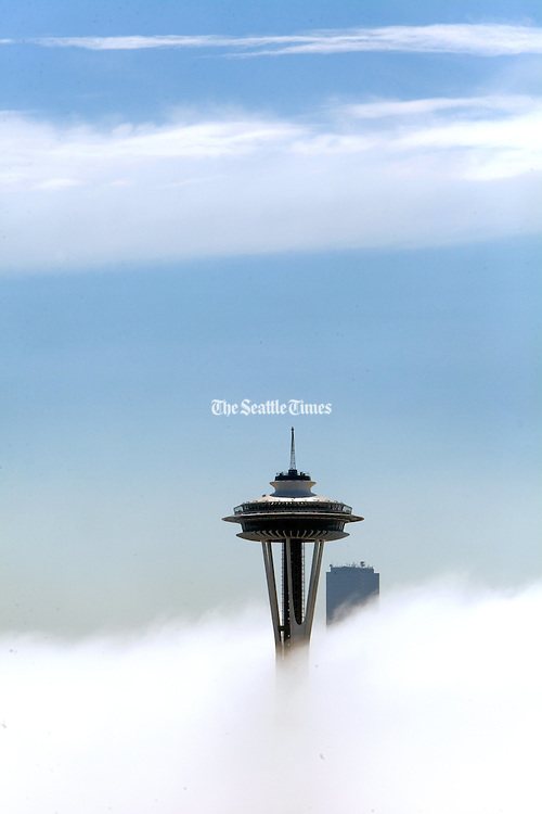 The Space Needle is nearly the only structure visible along the Seattle skyline due to heavy fog. <br />