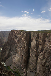 View of the Black Canyon and the Gunnison River and the Painted Wall from the South Rim Road.  Black Canyon of the Gunnison National Park is a United States National Park located near Montrose, Colorado in the western part of the state. The park is managed by the National Park Service. There are two entrances to the park; the more-developed south rim entrance is located 15 miles (24 km) east of Montrose, while the north rim entrance is located 11 miles (18 km) south of Crawford and is closed in the winter. The park contains 12 miles of the 48 mile long canyon of the Gunnison river. The park contains the deepest and most dramatic section of the canyon, one of the deepest mountain descents in North America.  The canyon continues upstream into the Curecanti National Recreation Area and downstream into the Gunnison Gorge National Conservation Area.