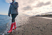 Taylor walks in new red rain boots along the ocean at Island View Regional Park near Victoria, BC Canada
