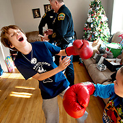 Nathan Norman and his sister Sarah play in the living room while being visited by police officers from Sparansburg County Police Department.