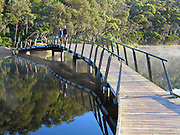 """Travelers relax on a boardwalk bridge over Tidal River at Wilson's Promontory National Park in the Gippsland region of Victoria, Australia. Natural tannins leached from decomposing vegetation turn the water brown. Drive two hours from Melbourne to reach Wilson's Promontory, or """"the Prom,"""" which offers natural estuaries, cool fern gullies, magnificent and secluded beaches, striking rock formations, and abundant wildlife."""
