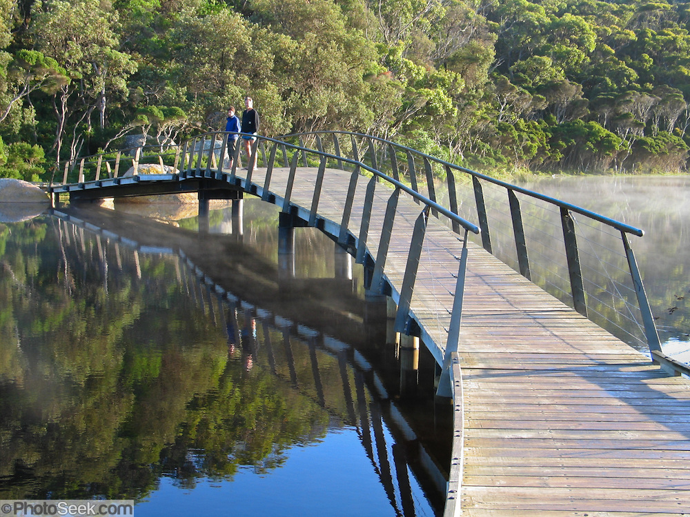 "Travelers relax on a boardwalk bridge over Tidal River at Wilson's Promontory National Park in the Gippsland region of Victoria, Australia. Natural tannins leached from decomposing vegetation turn the water brown. Drive two hours from Melbourne to reach Wilson's Promontory, or ""the Prom,"" which offers natural estuaries, cool fern gullies, magnificent and secluded beaches, striking rock formations, and abundant wildlife."