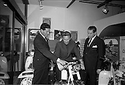 26/06/1967<br /> 06/26/1967<br /> 26 June 1967<br /> Motoring Enthusiasts Week officially opened by Joe Lynch at the International Trade Promotion Centre, Dublin. Image shows Joe Lynch sitting on a Garelli50cc. racing model, chatting with Mr. Patrick McCarthy, (left) Managing Director, Agrati Sales (Ireland) Ltd. and Mr. Noel Coade, Managing Director, International Trade Promotion Centre.