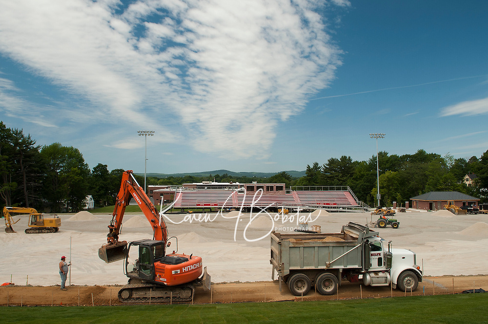 Crews are busy working on the Laconia High School football field prior to the turf installation on Friday morning.  (Karen Bobotas/for the Laconia Daily Sun)