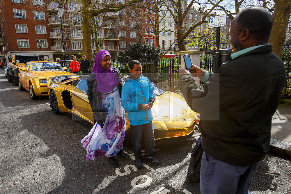 © Licensed to London News Pictures. 30/03/2016. London, UK. People having their pictures taken with a fleet of supercars covered in gold chrome wrap parked in Knightsbridge, London on Wednesday, 30 March 2016. Cars believed to be owned by a tourist from Saudi Arabia. Photo credit: Tolga Akmen/LNP