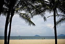Two coconut palms frame a view of Cua Dai Beach in Hoi An, Vietnam, Southeast Asia