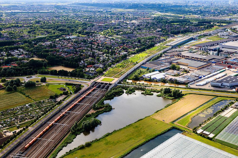 Nederland, Zuid-Holland, Barendrecht, 15-07-2012; een goederentrein die rijdt op de Betuweroute verlaat de Overkapping Barendrecht. Op het dak van de overkapping is o.a. een vlinderpark aangelegd en ook het station (rechts van het midden) maakt er deel van uit. De constructie is gebouwd over 9 spoorlijnen, waaronder naast de Betuweroute de HSL en dient om geluidsoverlast tegen te gaan. Rechts bedrijventerrein Dierenstein..The railway station is part of the covering-over of the HST in Barendrecht (SW Netherlands) . Roof landscape has a parking lot and a butterfly garden. A freight train is just passing by. .luchtfoto (toeslag), aerial photo (additional fee required).foto/photo Siebe Swart