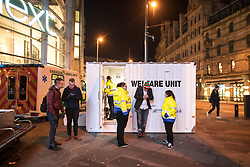 "© Licensed to London News Pictures . 16/12/2017. Manchester, UK. A mobile "" welfare unit "", offering people tea, coffee and medical support, is placed alongside an ambulance , on the pavement opposite the Printworks nightclub venue . Revellers out in Manchester City Centre overnight during "" Mad Friday "" , named for historically being one of the busiest nights of the year for the emergency services in the UK . Photo credit: Joel Goodman/LNP"