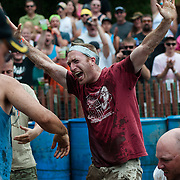 A man celebrates after successfully getting a pig to the center of the ring in under sixty seconds during the 28th annual Hog Wrestling Competition at Caldron Falls Bar in Twin Bridge, Wis., on July 20, 2013. Lukas Keapproth/Press Gazette Media