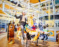Garden City, New York, USA. March 9, 2019.  Unveiling ceremony of mural by painter Michael White, of close-up of a Nunley's Carousel horse , is held at historic Nunley's Carousel in its Pavilion on Museum Row on Long Island. After speeches by elected officials and members of Baldwin Civic Association and Baldwin Historical Society, and others, people enjoy free carousel rides and food.
