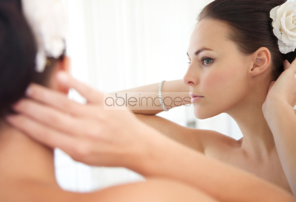 Mirror Image of Woman Adjusting Hair