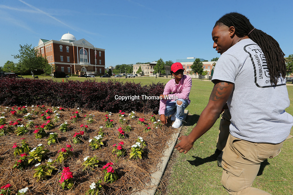 Alex Norwood, right, shows Lance Fernando a few tricks about maintaining a flower bed and keeping it looking nice as part of the City of Tupelo's Plant-A-Seed program.