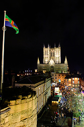 Images of the 2019 Lincoln Christmas Market taken from the wall walk at Lincoln Castle looking towards Lincoln Cathedral with visitors to the market in Castle Square, with the Lincolnshire Flag visible. <br /> <br /> Picture: Chris Vaughan Photography<br /> Date: December 6, 2019