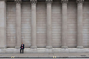 A young businessman checks messages on his phone beneath the columns of the Bank of England on Threadneedle Street in the City of London, the capital's financial district, on 3rd May 2019, in London, England