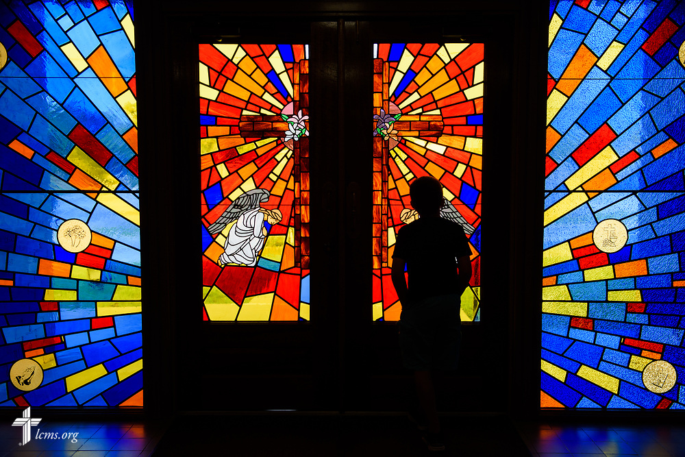 Gabe Qualman looks out the stained glass door before Divine Service at Mt. Calvary Lutheran Church, La Grange, Texas, on Sunday, Sept. 3, 2017. Last week, only a handful of church members who weren't trapped by the floodwaters made it to worship. A week after Hurricane Harvey the pews filled up again after the waters receded. LCMS Communications/Erik M. Lunsford