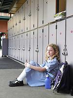 Elementary schoolgirl sitting on floor against school lockers portrait