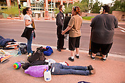 17 OCTOBER 2011 - PHOENIX, AZ:   A protester sleeps on the sidewalk while other Occupy Phoenix protesters start moving around early Monday in Phoenix. About 40 people spent Sunday night on the sidewalks around the Cesar Chavez Plaza in Phoenix, AZ, the defacto headquarters of the Occupy Phoenix protest. Early Monday morning they got up to continue their chants and protests against Wall Street, the growing income gap between rich and poor in the US, and money in politics. Monday marks the third day of Occupy Phoenix.  PHOTO BY JACK KURTZ