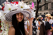 New York, NY - April 16, 2017. A young woman wears a  wide-brimmed hat with a floral arrangement that trails down the back at New York's annual Easter Bonnet Parade and Festival on Fifth Avenue.