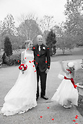 Bride and groom in black and white with flower girl throwing red rose petals over them.