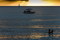 Swimmers and recreational boaters enjoy the sunset on Hanalei Bay on the island of Kauai near the north shore town of Hanalei in Hawaii.