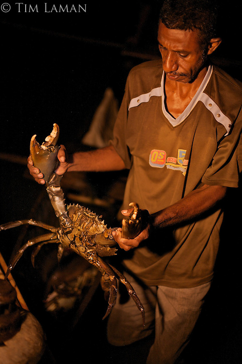Men spearfishing at night from the bows of canoes in Mayalibit Bay...Silas, headman of Kabilo Village captures a giant mud crab.
