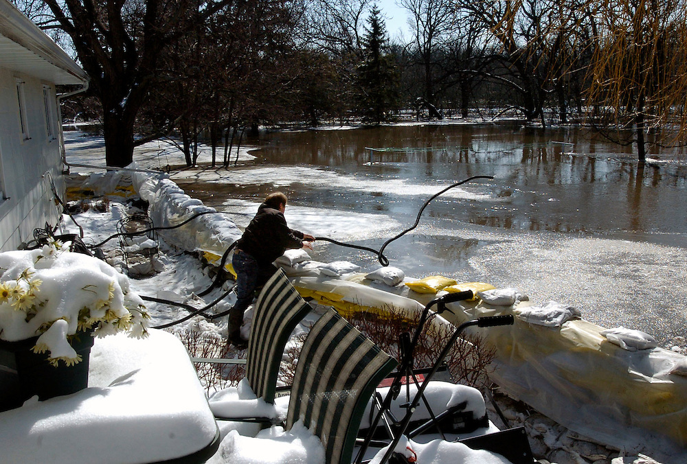 Rocky Swanson tosses a hose into the Red River to pump water out of the basement of his Oakport Township home north of Moorhead. Swanson returned home Saturday after evacuating Thursday.