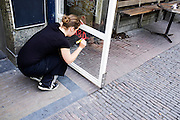 Een medewerkster van Kafe België in Utrecht schrijft een mededeling op een glazen bord voor het café.<br /> <br /> An employee of the cafe België in Utrecht is writing notes on a glass board.