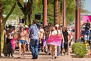 26 MARCH 2012 - PHOENIX, AZ:  A television photographer records a march of topless women and men in Phoenix Sunday. About 40 people marched through central Phoenix Sunday to call for a constitutional amendment to give women the same right to go shirtless in public that men have. The Phoenix demonstration was a part of a national Topless Day of Protest. Phoenix prohibits women from going topless in public so protesters, women and men, covered their nipples and areolas with tape. The men did it to show solidarity with the women marchers.   PHOTO BY JACK KURTZ