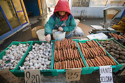 A vendor displays garlic and carrots at the Central Market in the city if Riga, Latvia.  Riga's Central Market, established in 1201, is one of Europe's largest and most ancient markets.