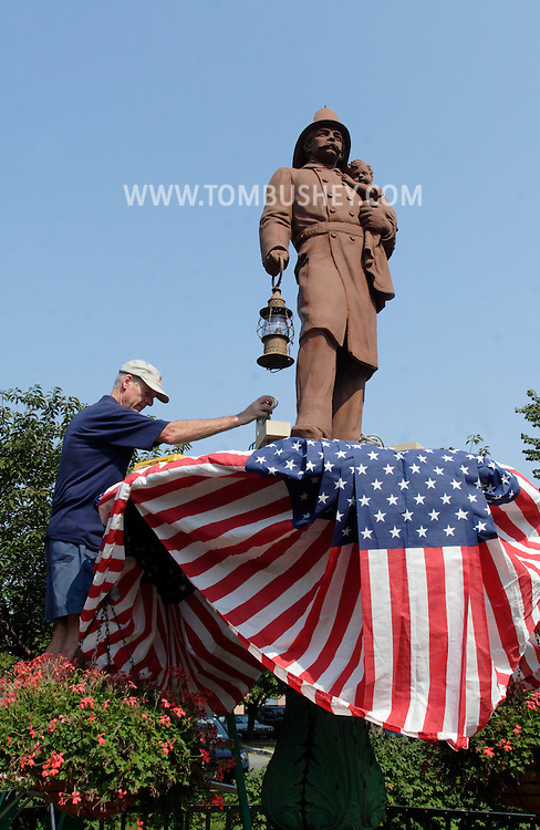 Middletown, NY - Don Wells attaches red, white and blue bunting to a statue of a fireman in preparation for the firefighters parade on  Sept. 7, 2007.