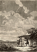 Artist's impression of the Benjamin Franklin's (1706-1790) investigation of the electrical nature of lightning, made at Philadelphia, USA, in September 1752.  Franklin and his assistant are flying a kite in a thunderstorm and Franklin is drawing a spark off the kite string.  Engraving from'Les Merveilles de a Science' by Louis Figuier (Paris, c1870).