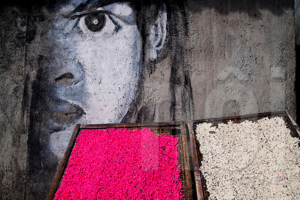 The intense gaze of a graffiti portrait behind trays of rice dyed for a festival in Bali, Indonesia, Southeast Asia
