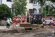 Local contractors help with the aftermath following a burst water main which closed the otherwise busy junction of Half Moon Lane and Dulwich Road in the south London area of Herne Hill. Emergency services were called at about 5am, when water inundated local businesses, forcing shopkeepers and owners to evacuate their properties and leave before electricity supplies were shut down. Copyright Richard Baker / Alamy Live News.