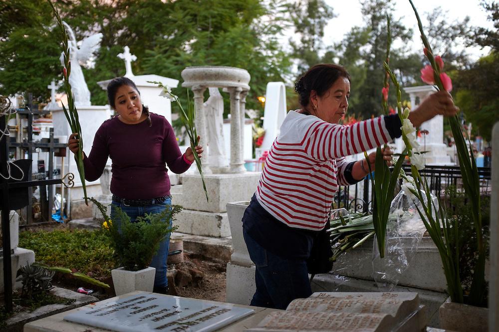 Family members pay respect to thier loved ones. Dia de los Muertos, San Miguel de Allende, Mexico.