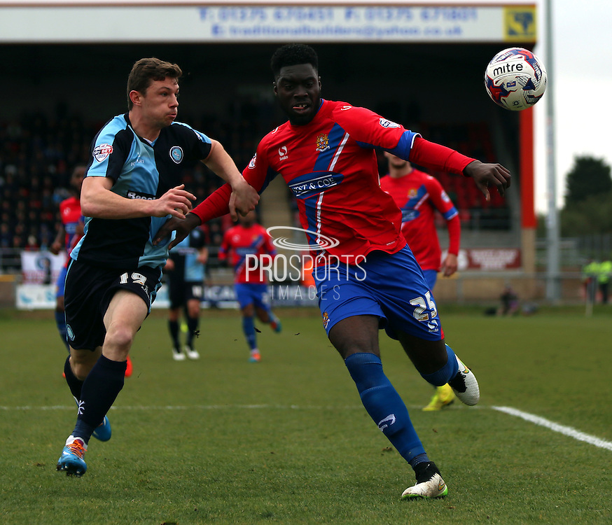 Matt McClure battling for ball with Ayo Obileye during the Sky Bet League 2 match between Dagenham and Redbridge and Wycombe Wanderers at the London Borough of Barking and Dagenham Stadium, London, England on 28 March 2015. Photo by Matthew Redman.